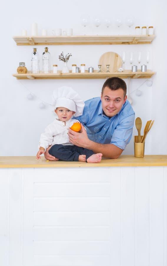 Vater- und Babysohn im Klagenchef werfen in der Hauptküche auf Glücklicher Familienvati, kleiner Sohn in der Kappe des Kochs stockfotografie