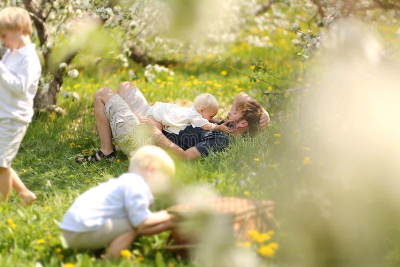Vater und drei Kinder, die am Picknick im Blumen-Obstgarten sich entspannen lizenzfreie stockfotos