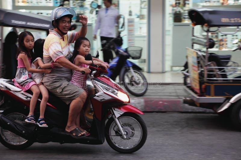 Vater und drei Töchter auf einem Roller stockbild