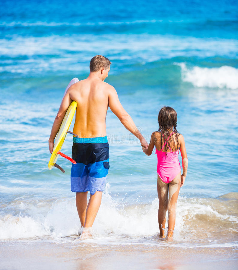 Vater und Duagher auf dem Strand-gehenden Surfen lizenzfreie stockfotografie
