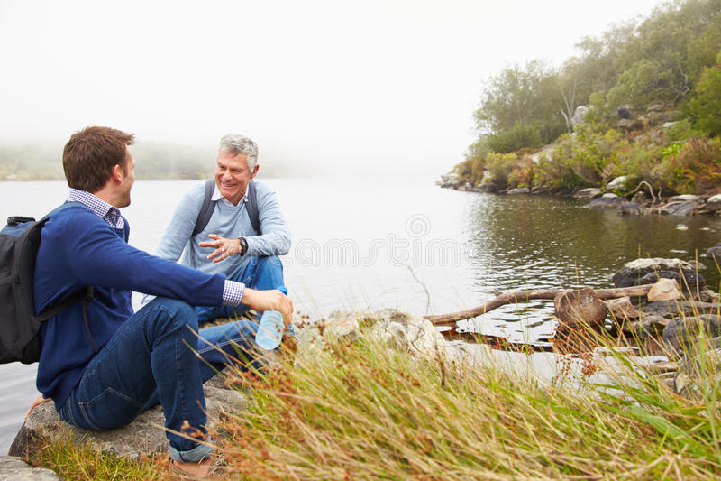 Vater und junger erwachsener Sohn, die durch einen See sprechen stockfotos