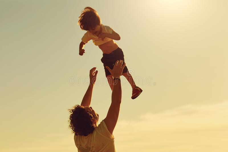Vater und Kind, die in der Natur bei Sonnenuntergang spielen stockbild