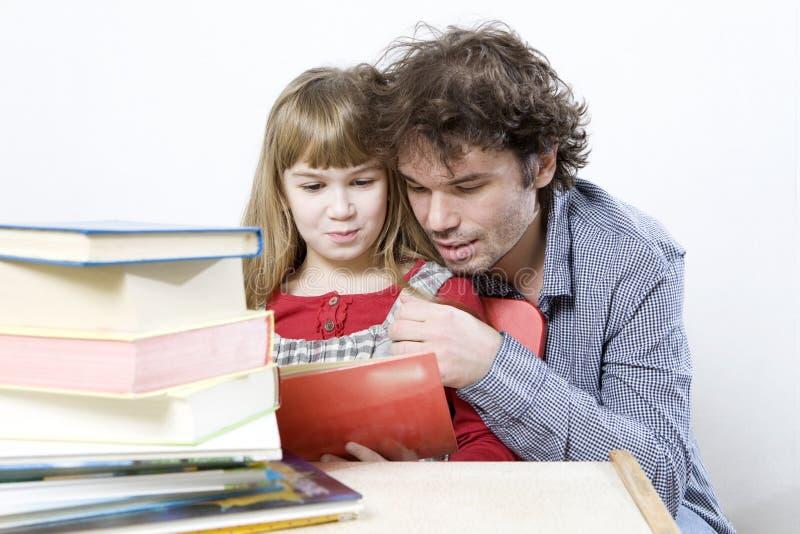 Vater und Kind, die ein Buch lesen. lizenzfreie stockfotografie