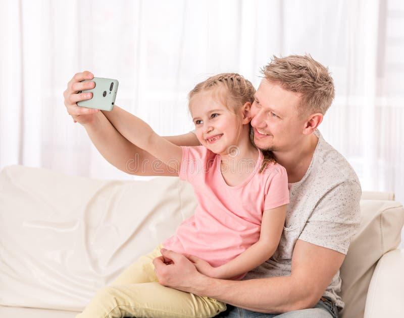 Vater und Kind nehmen selfie im Wohnzimmer stockbild