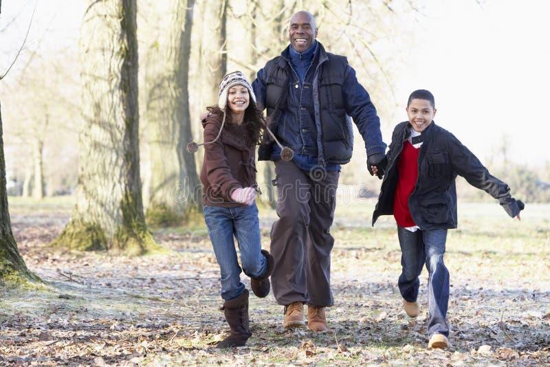 Vater und Kinder auf Herbst-Weg lizenzfreie stockfotos