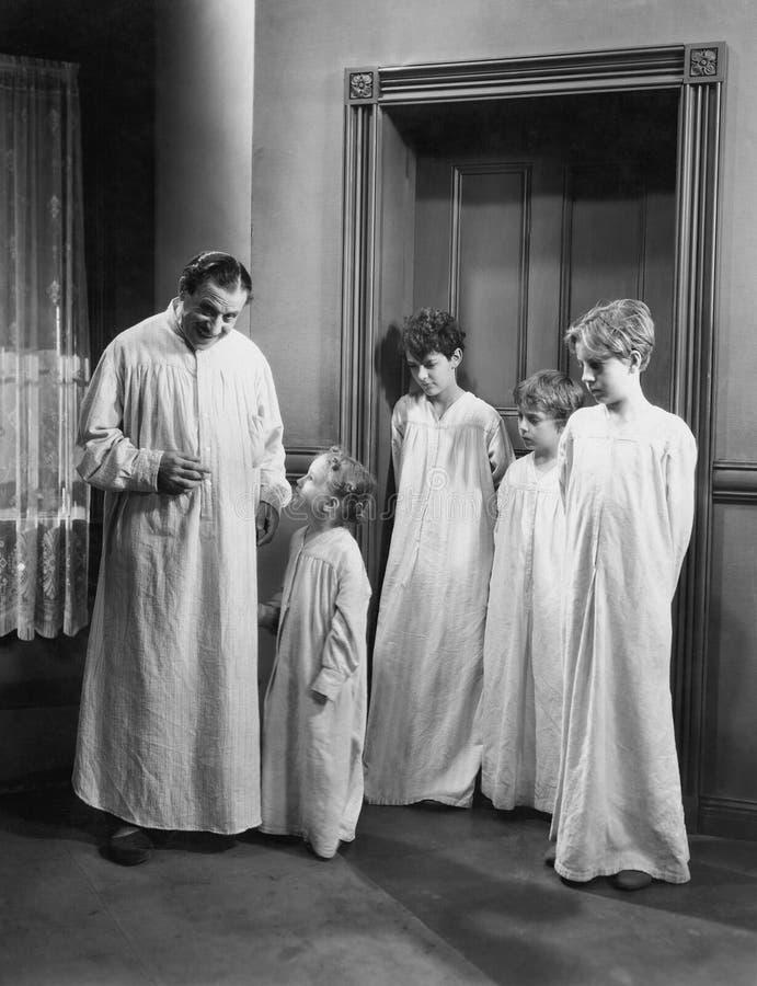 Vater und Kinder in den Nachthemden (alle dargestellten Personen sind nicht längeres lebendes und kein Zustand existiert Lieferan lizenzfreies stockbild