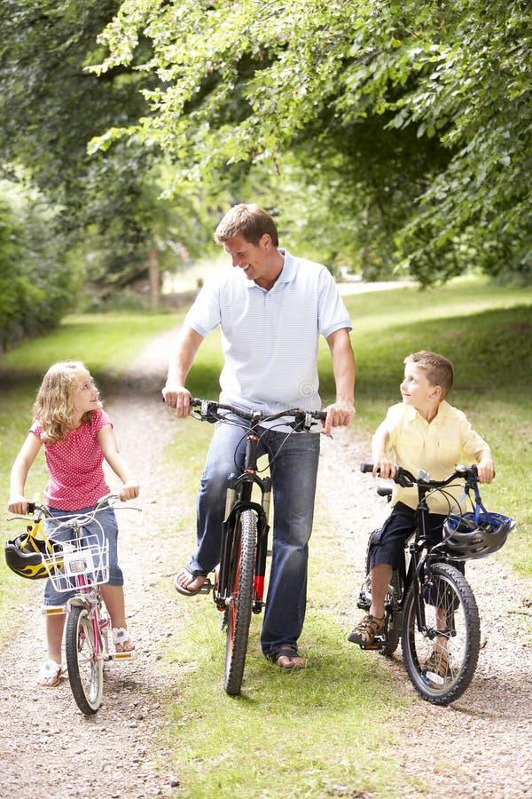 Vater und Kinder, die Fahrräder in der Landschaft reiten lizenzfreie stockfotografie