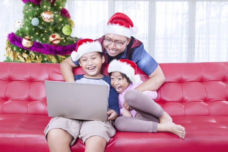 Vater und Kinder, die mit einem Laptop spielen lizenzfreie stockfotografie