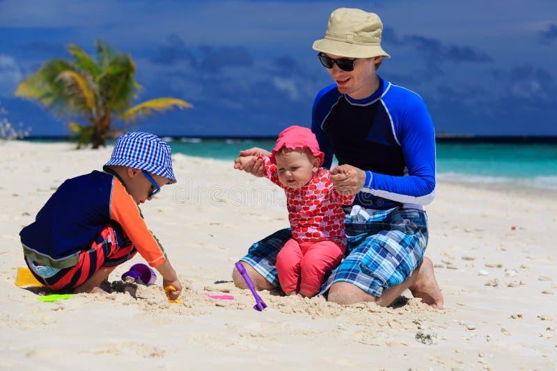 Vater und Kinder, die Sandburg am tropischen Strand machen stockfotografie