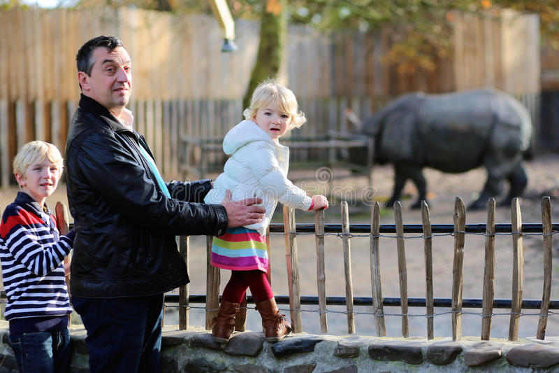 Vater und Kinder, die sonnigen Tag im Zoo genießen lizenzfreies stockbild