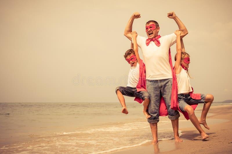Vater und Kinder, die Superhelden auf dem Strand am Tagesti spielen stockfotografie