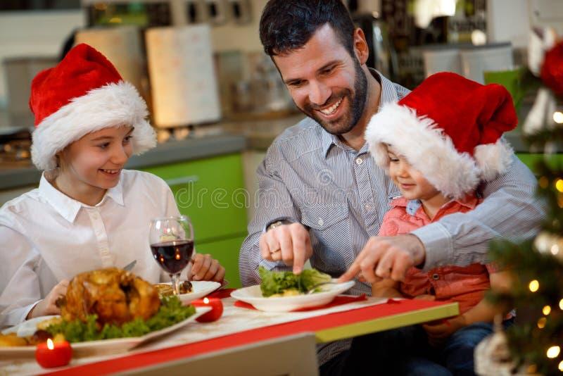 Vater und Kinder, die traditionelles Weihnachtsessen essen lizenzfreie stockfotografie