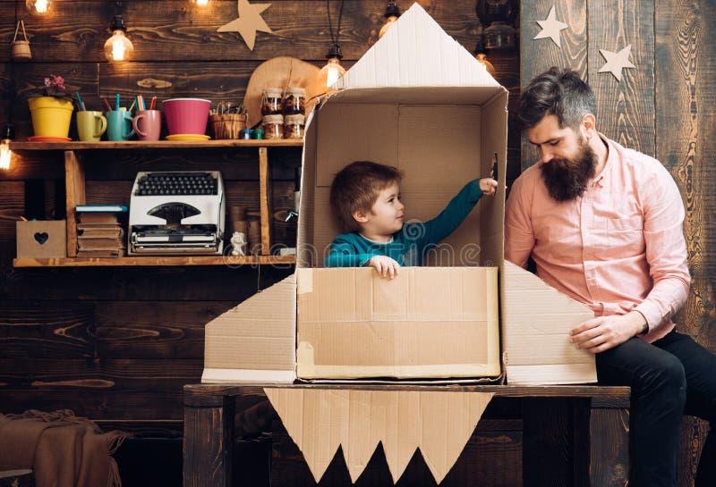 Vater und kleiner Junge in der Papierrakete Vater und Sohn spielen mit Rakete und dem Träumen über zukünftige Karriere stockfotografie