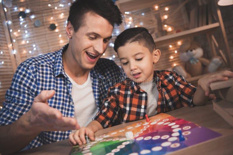 Vater und kleiner Sohn spielen Brettspiel nachts zu Hause lizenzfreies stockbild