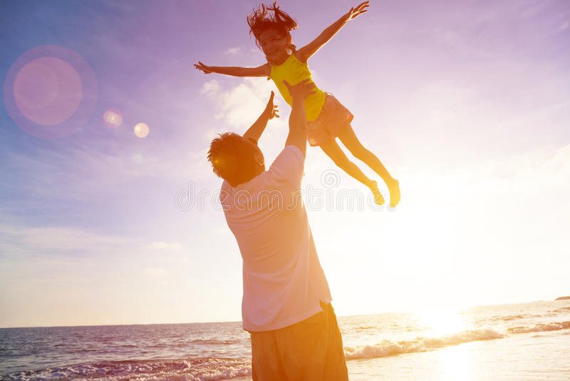 Vater und kleines Mädchen, die auf dem Strand spielen lizenzfreie stockfotos