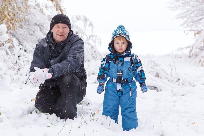 Vater- und Kleinkindjunge, der Spaß mit Schnee am Wintertag hat stockfotografie
