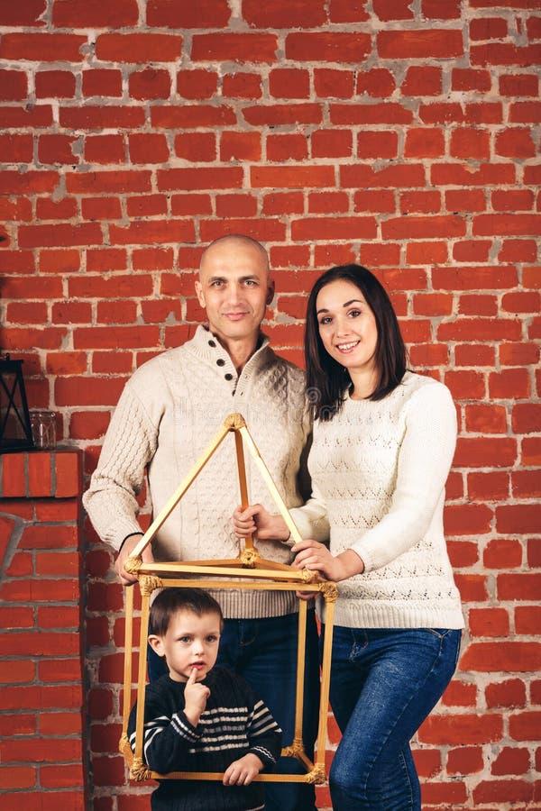 Vater und Mutter lächeln und Sohn lugt aus improvisiertem Haus im Studio heraus gegen Hintergrund der Backsteinmauer Kopieren Sie stockfotografie