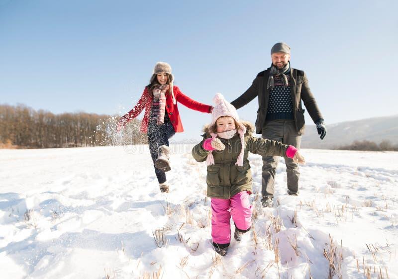 Vater und Mutter mit ihrer Tochter, spielend im Schnee lizenzfreie stockbilder