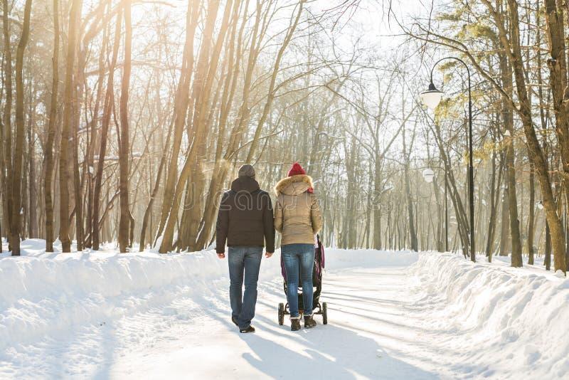Vater und Mutter mit Kinderwagen im Winterwald stockfoto