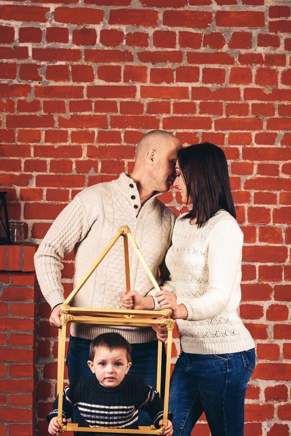 Vater- und Mutterkuß und Sohn späht aus einem improvisierten Haus im Studio auf Hintergrund der Backsteinmauer heraus Kopieren Si lizenzfreies stockbild