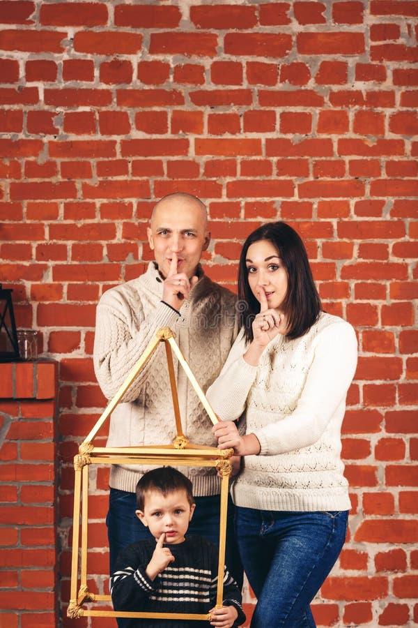 Vater- und Muttershow shh und Sohn zeigt shh von improvisiertem Haus im Studio auf Hintergrund der Backsteinmauer Kopieren Sie Pl stockbilder