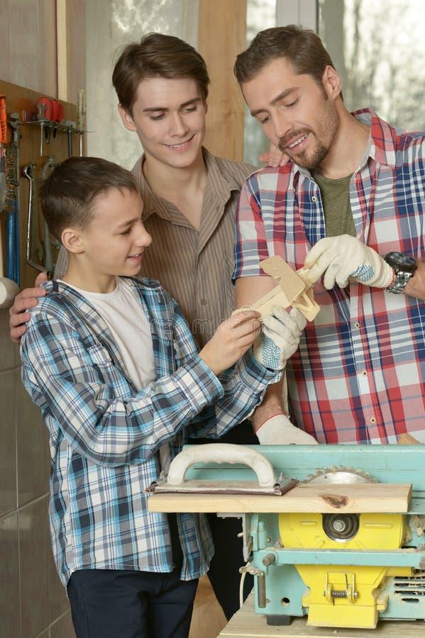 Vater und Söhne in der Werkstatt lizenzfreies stockfoto