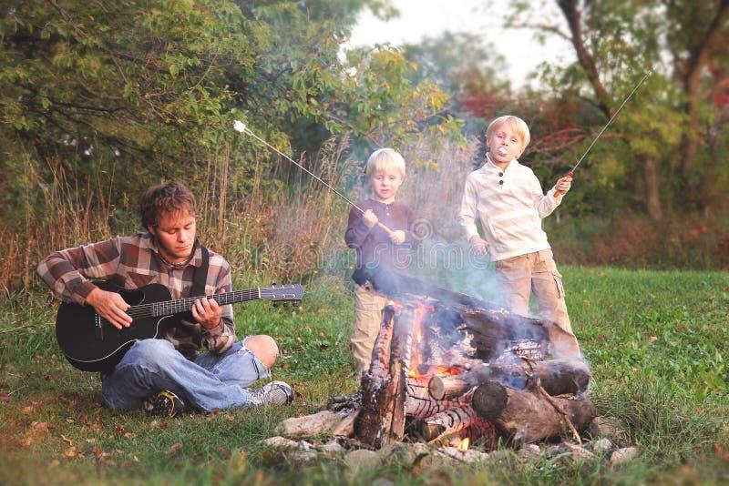 Vater und Söhne, die Eibische braten und Gitarre durch Lager spielen lizenzfreie stockfotos