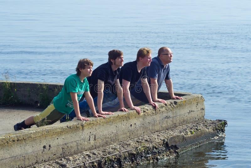 Vater und Söhne machen Liegestützübung lizenzfreies stockfoto