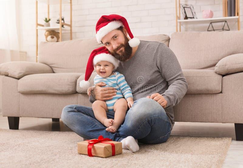 Vater und sein kleines Baby, die Sankt-Hüte tragen lizenzfreie stockfotos