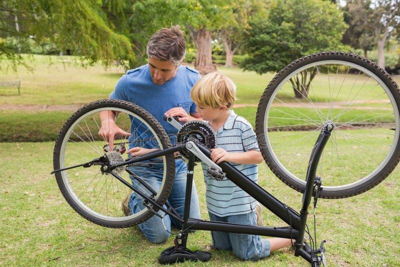 Vater und sein Sohn, die ein Fahrrad reparieren stockbild