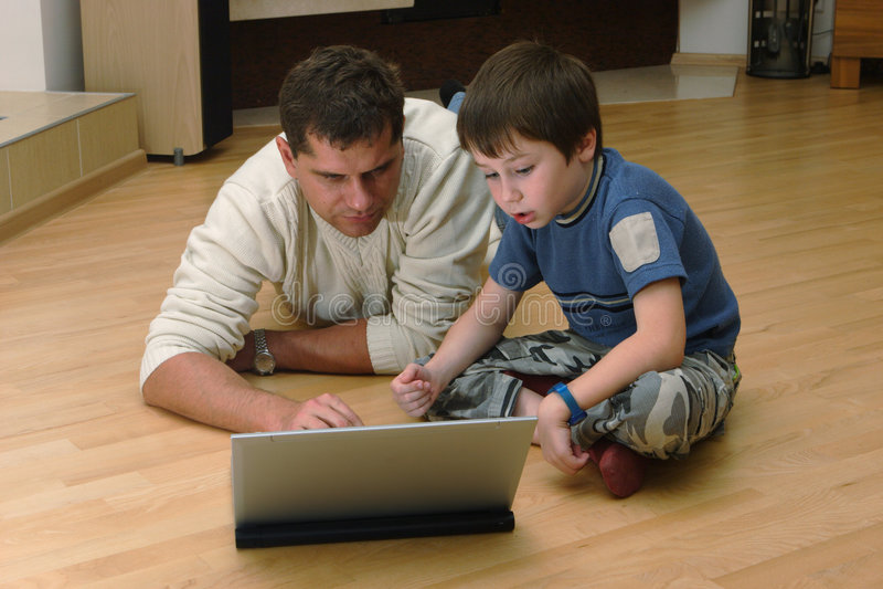 Vater und sein Sohn mit Laptop lizenzfreies stockbild