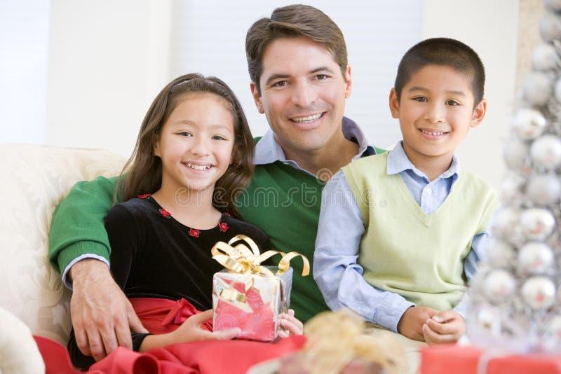Vater und sein Sohn und Tochter, die auf Sofa sitzen lizenzfreie stockbilder