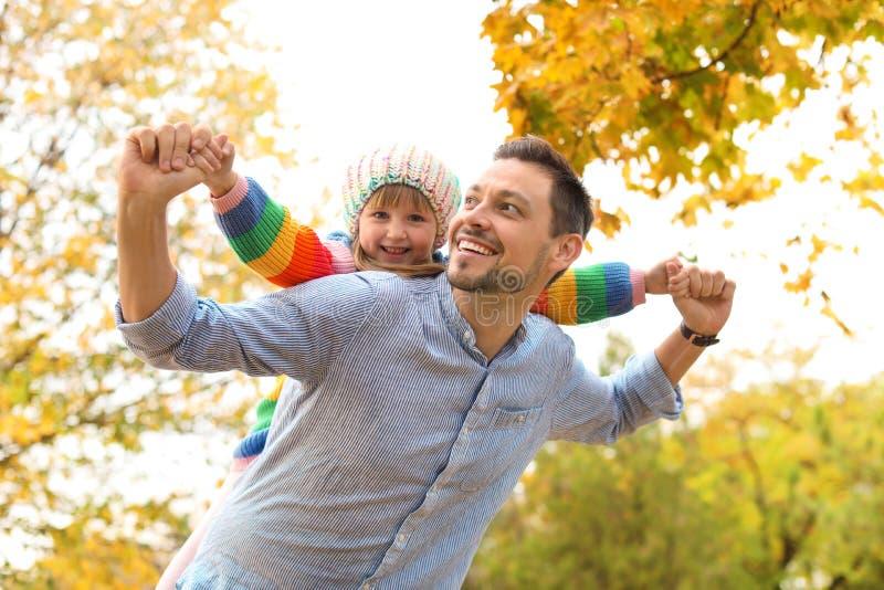 Vater und seine nette Tochter, die zusammen Zeit im Park verbringen stockfotografie