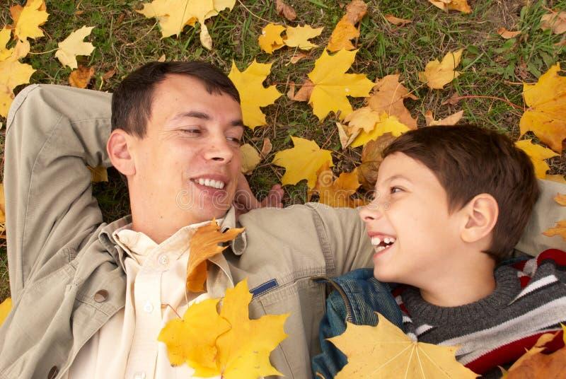 Vater und Sohn auf dem Gras stockbild