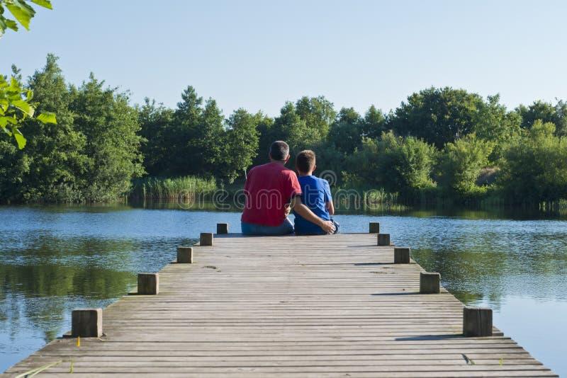 Vater und Sohn auf einem hölzernen Pier auf einem Teich lizenzfreie stockfotografie