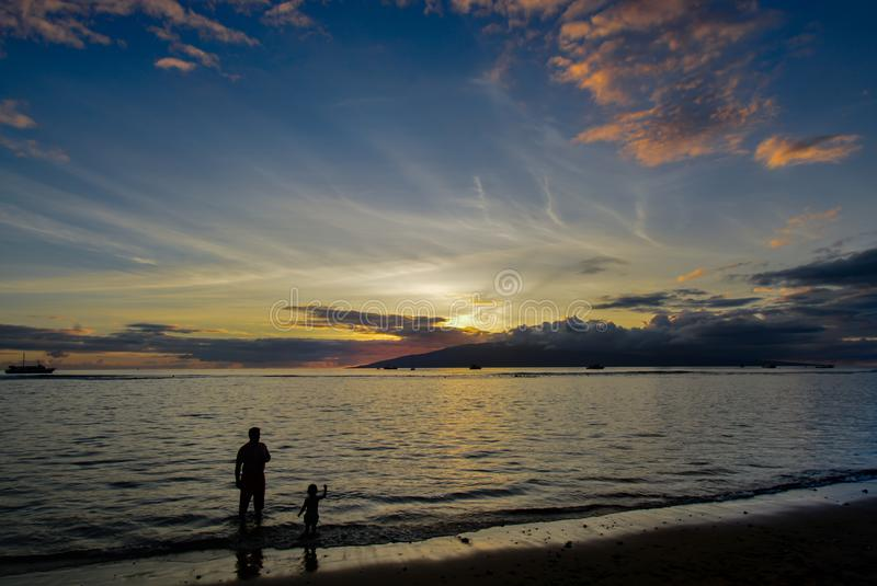 Vater und Sohn auf Lahaina setzen bei Sonnenuntergang auf den Strand lizenzfreie stockfotografie