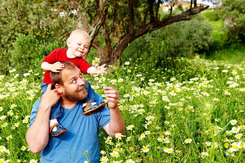 Vater und Sohn in den Blumen lizenzfreie stockbilder