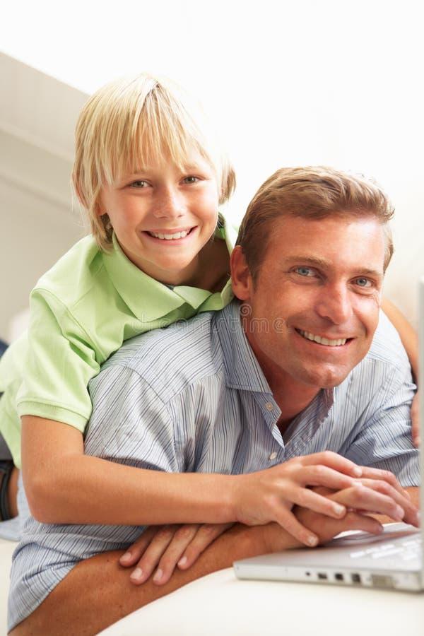 Vater und Sohn, der den Laptop sitzt auf Sofa verwendet stockbild
