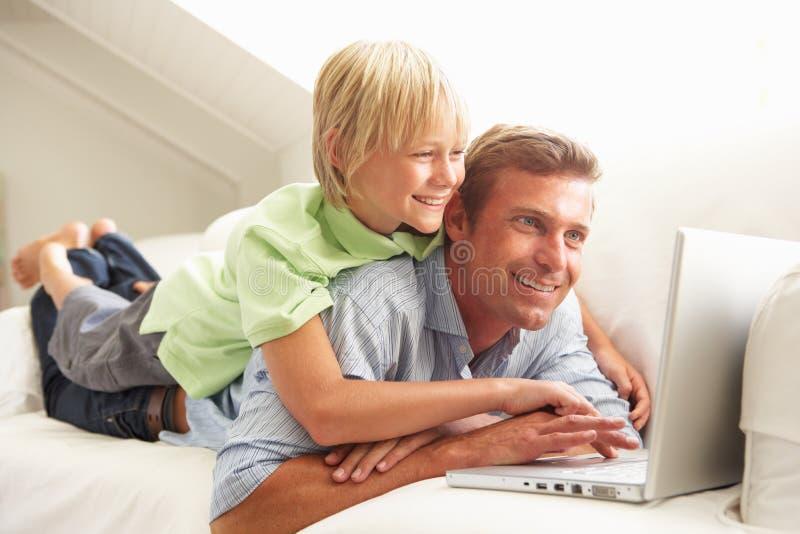 Vater und Sohn, der den Laptop sitzt auf Sofa verwendet lizenzfreie stockbilder