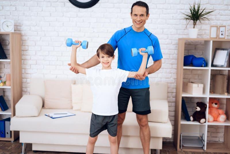 Vater und Sohn, die Übungen mit Dummköpfen tun lizenzfreie stockbilder