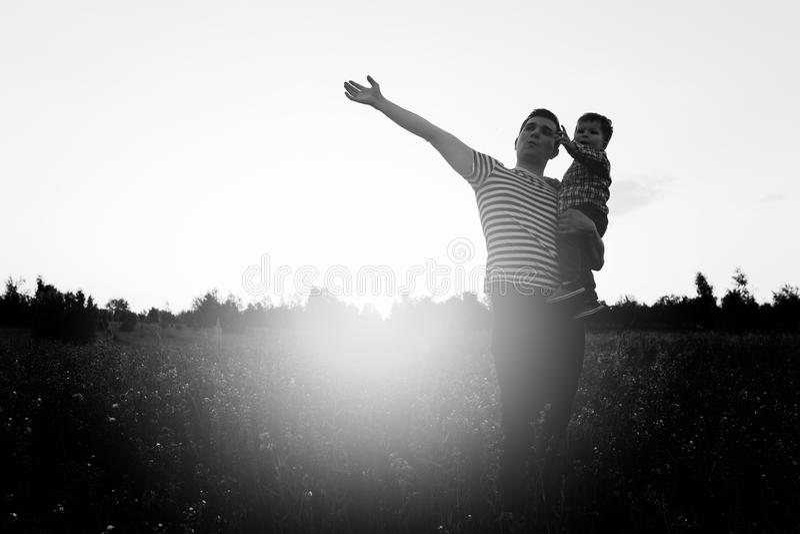 Vater und Sohn, die auf dem Gebiet zur Sonnenuntergangzeit spielen Bemannen Sie das Halten des kleinen Jungen auf Händen und das  lizenzfreie stockbilder
