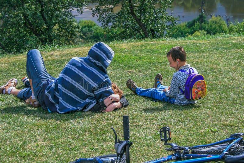 Vater und Sohn, die auf dem Gras des Hügels liegen Entspannungsleute im Stadtpark stockbilder