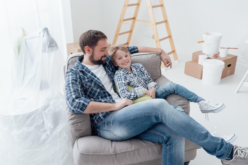 Vater und Sohn, die auf dem Lehnsessel sich entspannen lizenzfreie stockfotografie