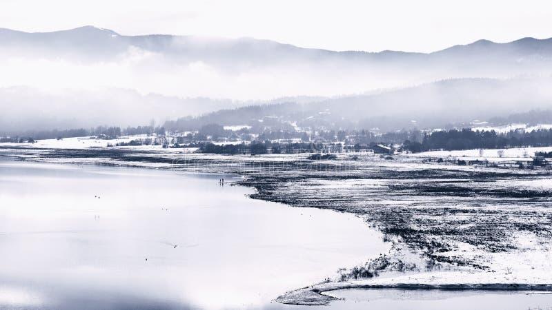 Vater und Sohn, die auf dem Ufer in der kalten Winterlandschaft zahlen lizenzfreies stockfoto