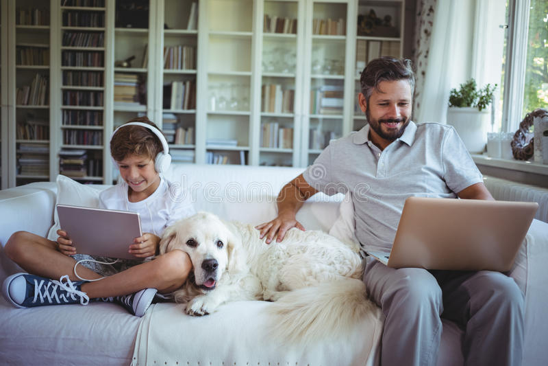 Vater und Sohn, die auf Sofa sitzen und digitale Tablette und Laptop verwenden lizenzfreies stockfoto