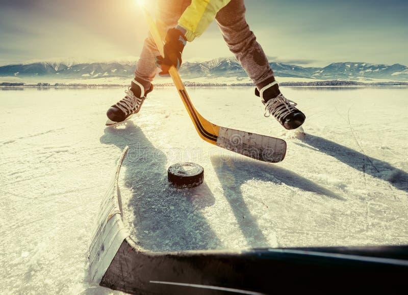 Vater und Sohn, die das Hockey auf dem gefrorenen hoher Gebirgsla spielen lizenzfreie stockfotografie