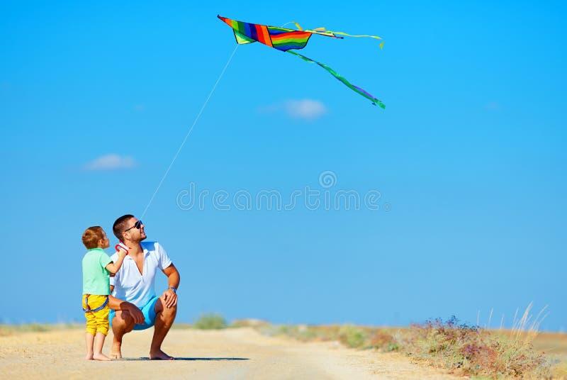 Vater und Sohn, die den Spaß, zusammen spielend mit Drachen hat stockbild