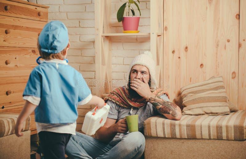 Vater und Sohn, die Doktor-, Gesundheitswesen- und Behandlungskonzept spielen Besuchspatient des Notmedizinischen Spezialisten zu stockbild