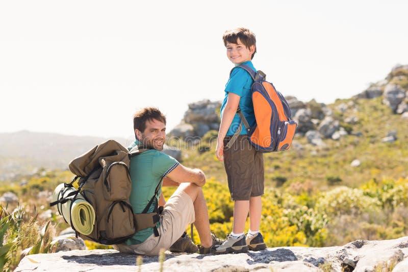 Vater und Sohn, die durch Berge wandern stockfotografie