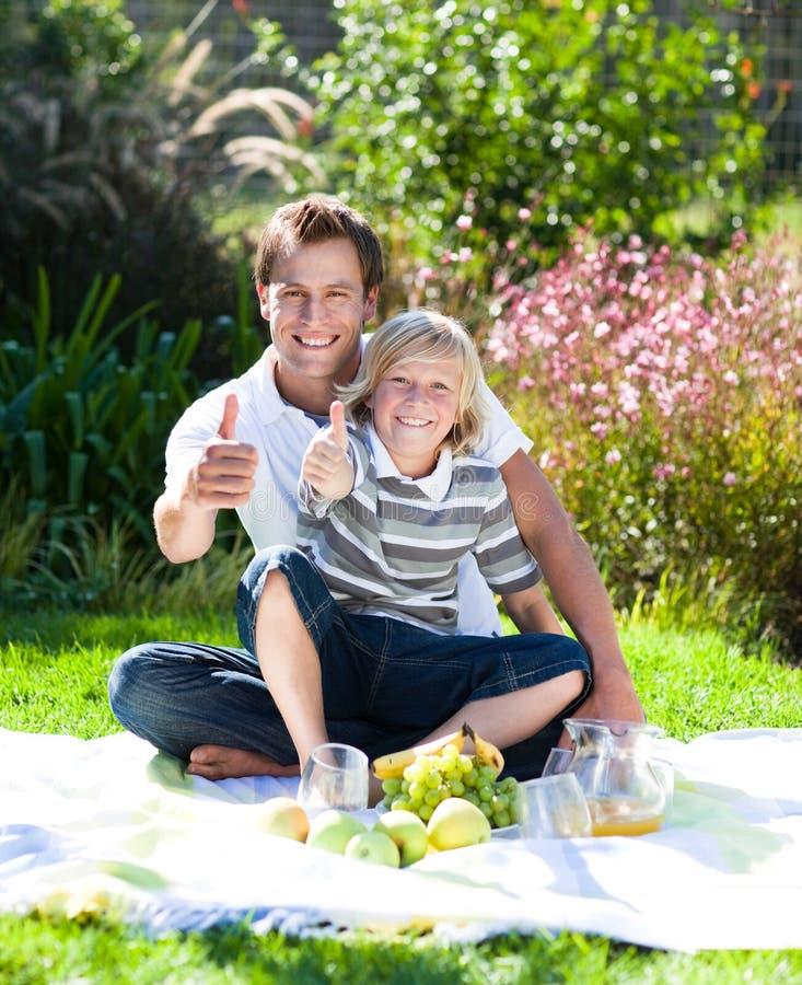 Vater und Sohn, die ein Picknick mit den Daumen oben haben lizenzfreie stockfotos